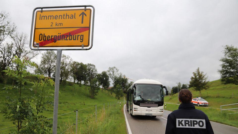 Eine Mitarbeiterin der Kripo geht auf den am Straßenrand stehenden Linienbus zu.