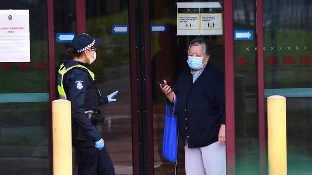 Eine Polizistin spricht mit einerBewohnerin am Eingang einerWohnsiedlung