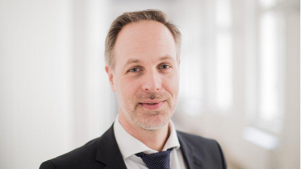 Ein Mann in schwarzem Jackett lächelt mit grau-blonden Haaren und Dreitagebart in die Kamera. Er hat blaue Augen