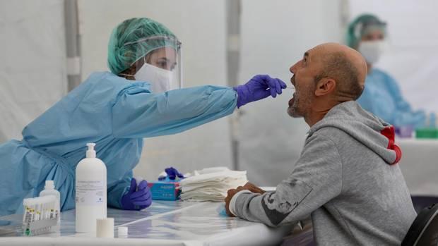 Gesundheitsamts-Mitarbeiterin macht einen Abstrich im Rachen eines Mannes