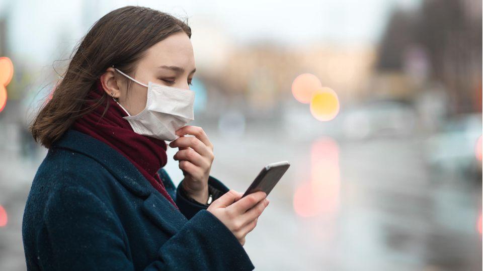 Eine Frau mit Mundschutz und Smartphone