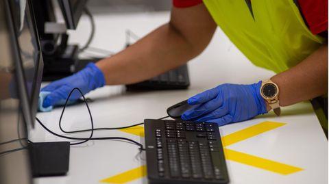 Eine Reinigungskraft desinfiziert einen Arbeitsplatz