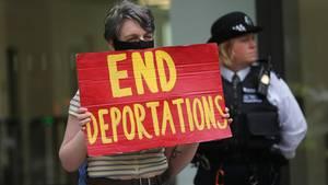 """Demonstrantin protestiert mit Schild """"End Deportations"""" gegen Abschiebungen"""