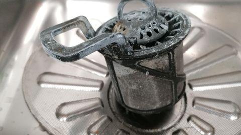 DiesesSieb ist nicht nur verschmutzt, schlechtes Waschmittel hat bereits den Kunststoff angegriffen.
