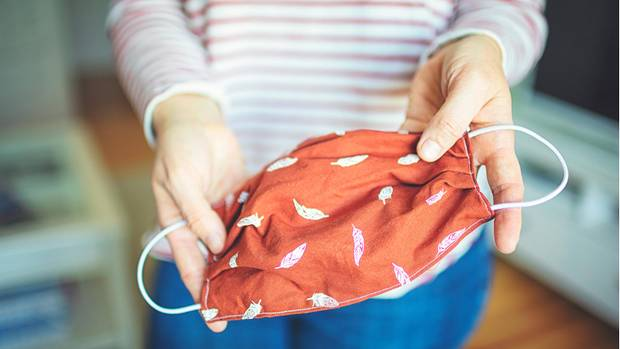 Eine Frau hält einen orangenen Mundschutz aus Baumwolle mit weißen Federn