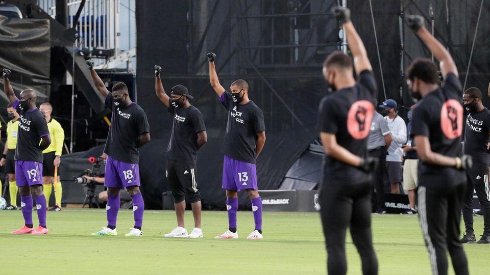 MLS-Profis heben vor dem Spiel ihre Fäuste als Zeichen gegen Rassismus