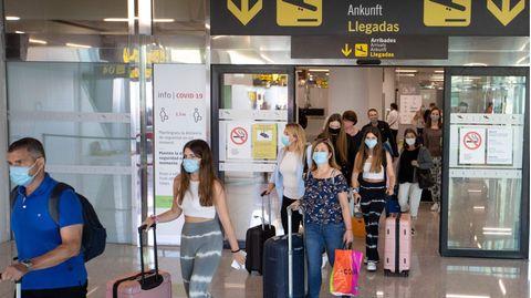Touristen mit Maskenschutz verlassen den Flughafen von Palma de Mallorca