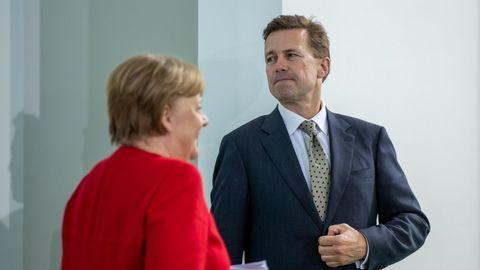 Angela Merkel geht in rotem Blazer an Pressesprecher Seibert in Anzug und Krawatte vorbei