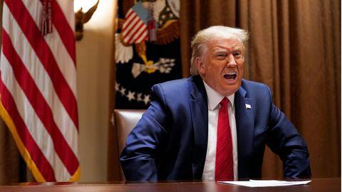 Us-Präsident Donald Trump sitzt in Anzug und Krawatte vor US-Flaggen an einem runden Tisch und spricht