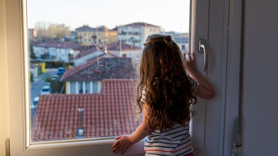 Kind schaut durchs Fenster