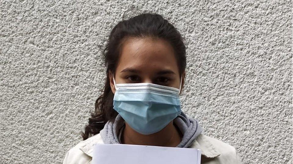 Eine junge Frau mit schwarzem Zopf steht mit Mundschutz vor einer verputzen Wand und hält sich ihr Abizeugnis vor die Brust