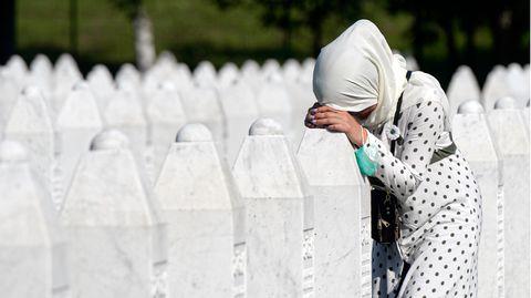 Eine Frau trauert auf dem Friedhof der Gedenkstätte Potocari in der Nähe von Srebrenica an einem Grab