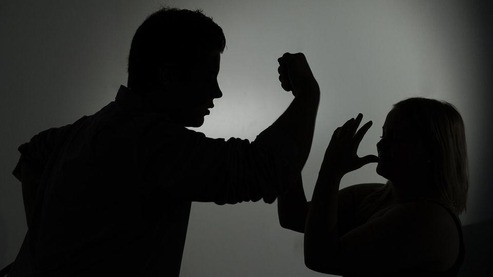 Häusliche Gewalt: Silhouette eines Mannes droht einer Frau mit der Faust (Symbolbild)
