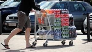 Ein Einkaufswagen voller Getränkedosen wird über den Parkplatz geschoben