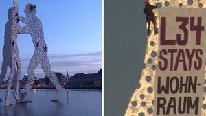 Aktivisten klettern auf dem Molecule Man in Berlin herum und bringen ein Transparent an