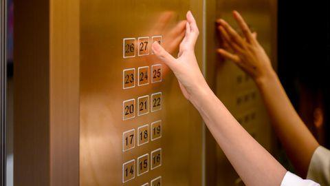 Eine Frau drückt Knöpfe im Fahrstuhl