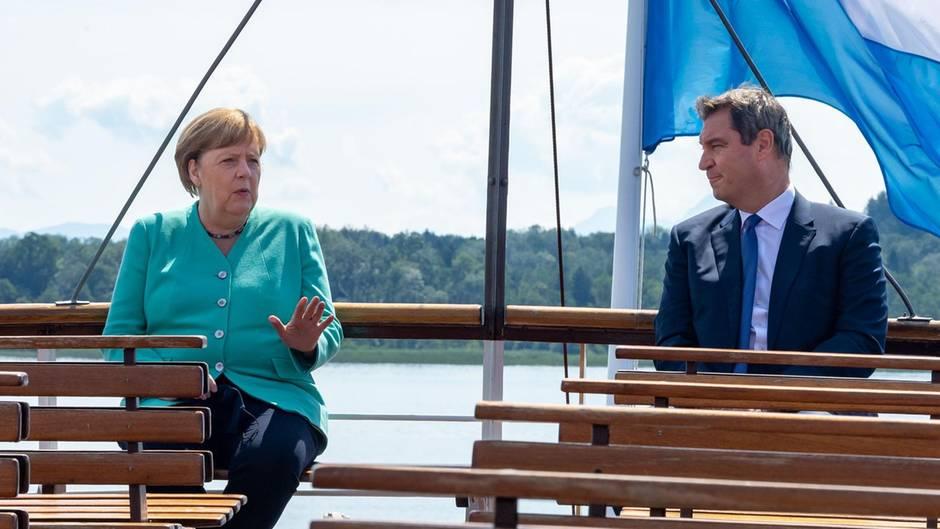 Unter einer weißblauen Flagge sitzen Angela Merkel und Markus Söder am Heck eines Schiffes in der Sonne