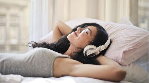 Frau hört Musik mit Kopfhörern auf dem Bett