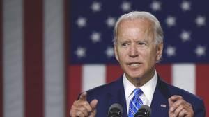 Joe Biden steht in Anzug und Krawatte am Rednerpult und gestikuliert mit beiden Händen. Im Hintergrund hängt eine US-Flagge