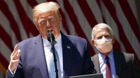 US-Präsident Donald Trump bei einer Rede, hinter ihm steht sein maskierter Gesundheitsexperte Anthony Fauci
