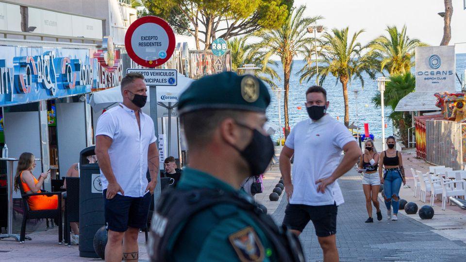 Beamte der Guardia Civil stehen Wache auf Mallorca:Die wilden Partys Hunderter Touristen ohne Schutzmaske und Sicherheitsabstand haben ein einschneidendes Nachspiel.Erstmals werden mitten im Sommer alle Vergnügungslokale im Herzstück des Ballermanns geschlossen.