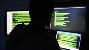 Ein Mann sitzt vor drei Bildschirmen mit Text