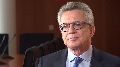 Thomasd de Maiziere sitzt in blauem Anzug und Krawatte neben einem Konferenztisch mit vielen Mikrofonen