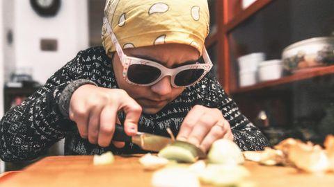 Ein Kind schneidet Zwiebeln mit Kopftuch und Brille auf