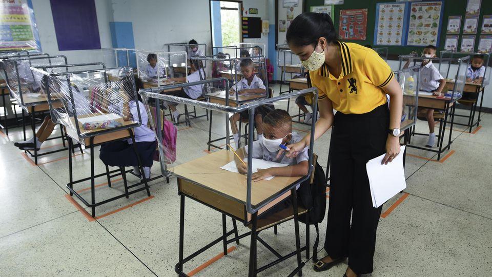 Coronavirus Thailand: Schüler sitzen hinter Trennwänden aus Plastik in einem Klassenzimmer