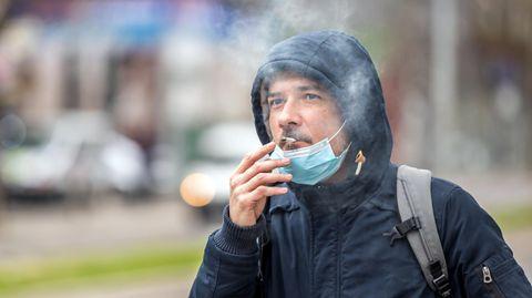 Coronavirus: Ein Mann raucht eine Zigarette