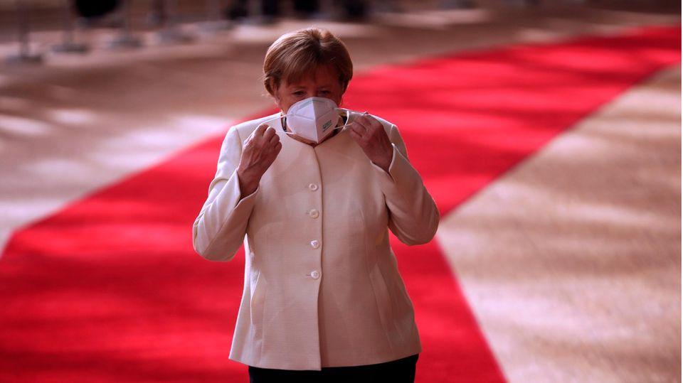 Angela Merkel setzt sich am Sonntag Morgen beim EU-Gipfel eine Maske auf.