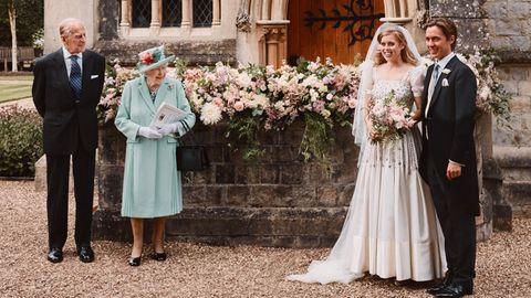 Vor einem Blumenbeet steht rechts ein Brautpaar und links Queen Elizabeth und Prinz Philipp. Im Hintergrund eine gotische Kirche