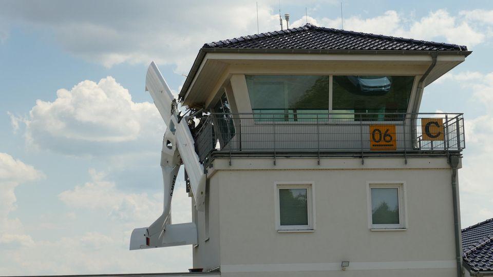 Ein Kleinflugzeug hängt nach einer Kollision am Tower des Flugplatzes Müncheberg-Eggersdorf (Landkreis Märkisch-Oderland).