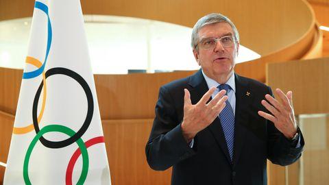 IOC-Präsident Bach steht und spricht vor einer Flagge mit den olympischen Ringen