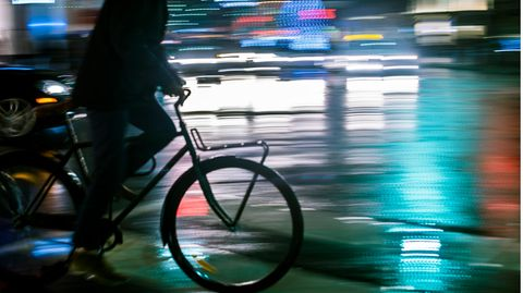 Ein Mann fährt nachts auf einem Fahrrad durch die Stadt