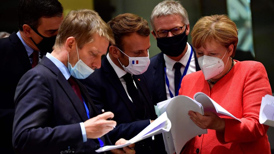 EU-Gipfel; Spaniens Premier Sanches, Frankreichs Präsident Macron und Kanzlerin Merkel beugen sich über die Papiere