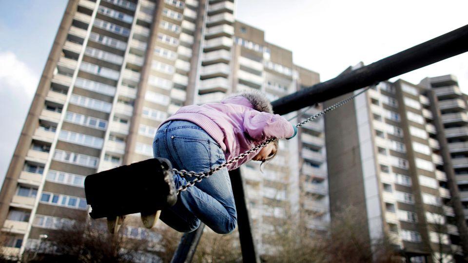 Ein Kind schaukelt vor einem Hochhaus in Köln