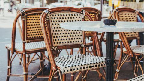 Stühle mit Tischen in einem Außenbereich eines Cafés