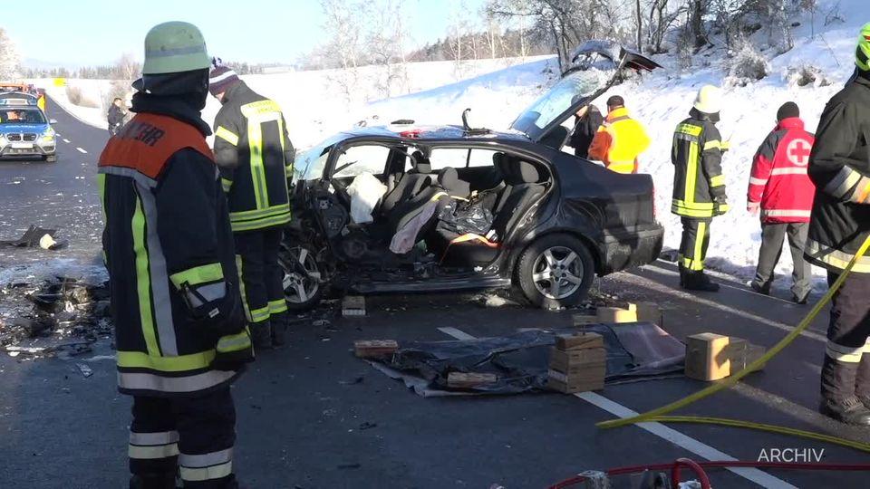 Feuerwehrleute stehen um ein Autowrack herum