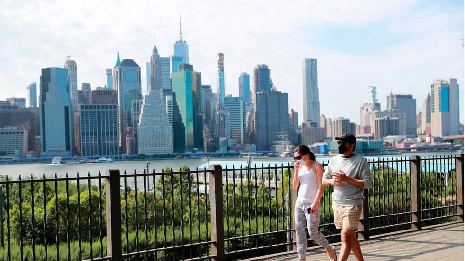Passanten tragen Schutzmasken und gehen in einem Park im New Yorker Stadtteil Brooklyn spazieren