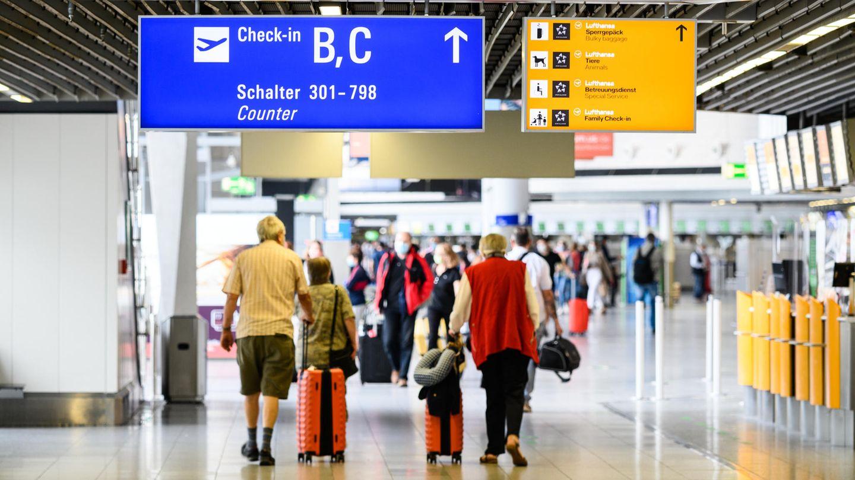 Reisende gehen am Flughafen Frankfurt mit Gepäck durch die Abflughalle im Terminal 1