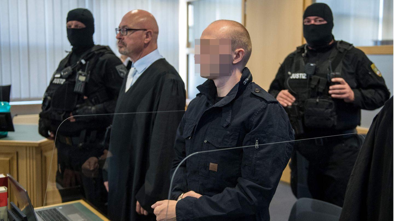 Der Angeklagte im Halle-Prozess im Gerichtssaal mit Anwalt und zwei Polizisten