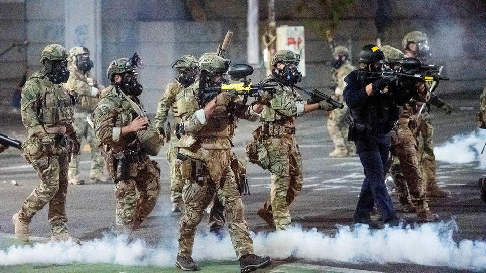 Bundespolizisten richten ihre Waffen auf Demonstranten