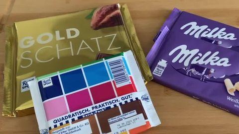 Auf einer hölzernen Tischplatte liegen links zwei quadratische Schokoladen von Ritter Sport, rechts zwei längliche von Milka