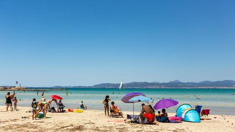 Urlauber sonnen sich an einem Strand auf Mallorca
