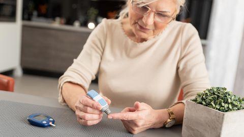 Eine Frau misst ihren Blutzuckerspiegel