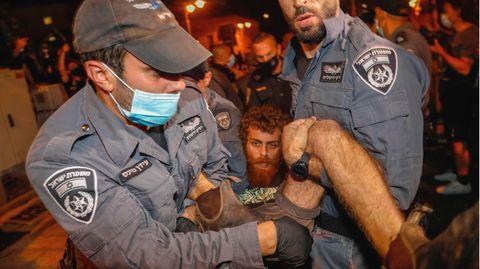 Zwei israelische Polizisten in grauen Uniformen mit Caps und Mundschutz ziehen einen Demonstranten weg