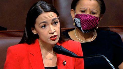Eine Frau mexikanischer Abstammung steht in rotem Blazer an Rednerpult und Mikro des US-Kongresses