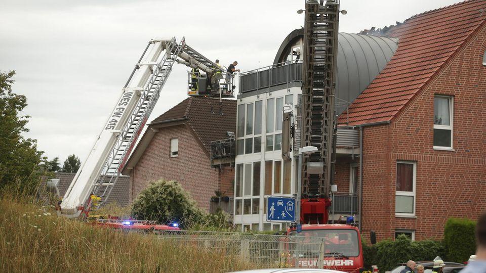 Mit Drehleitern verschaffen sich Einsatzkräfte Zugang zum beschädigten Dachstuhl des Hauses