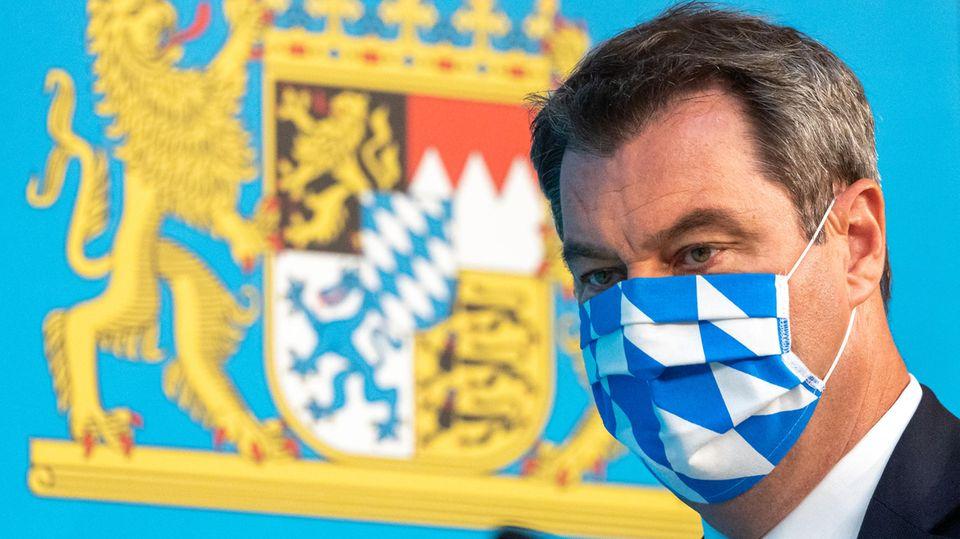 Bayerns Ministerpräsident Markus Söder mit weiß-blauer Gesichtsmaske vor bayerischem Wappen